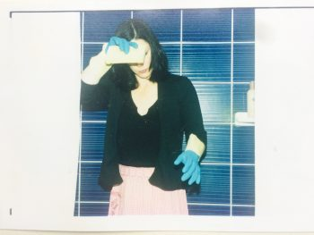 woman wearing cleaning gloves against tile wall