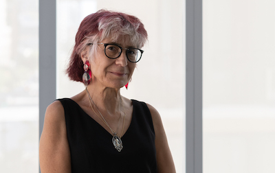 woman with chin length gray and reddish hair in black sleeveless dress and glasses with silver pendant against white wall